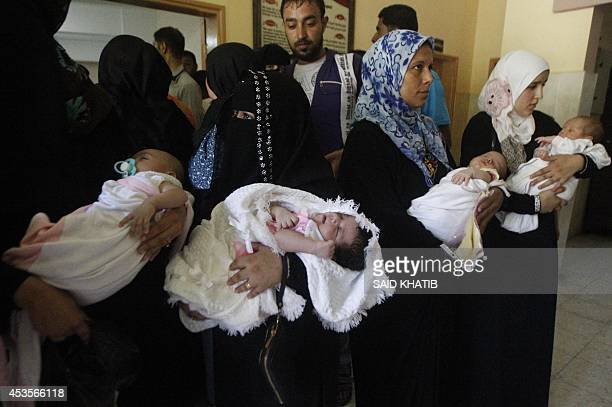 Palestinian displaced mothers carry their newborns at an United Nations Relief and Work Agency centre on August 13 2014 in Rafah in southern Gaza...