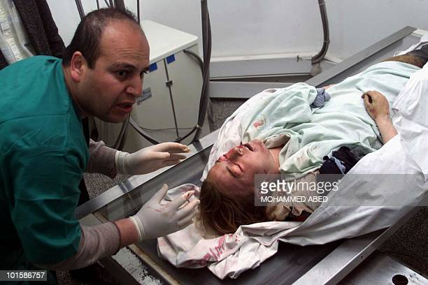A Palestinian doctor stands over the body of US peace activist Rachel Corrie at alNajar hospital in Rafah town 16 March 2003 Corrie of Washington DC...