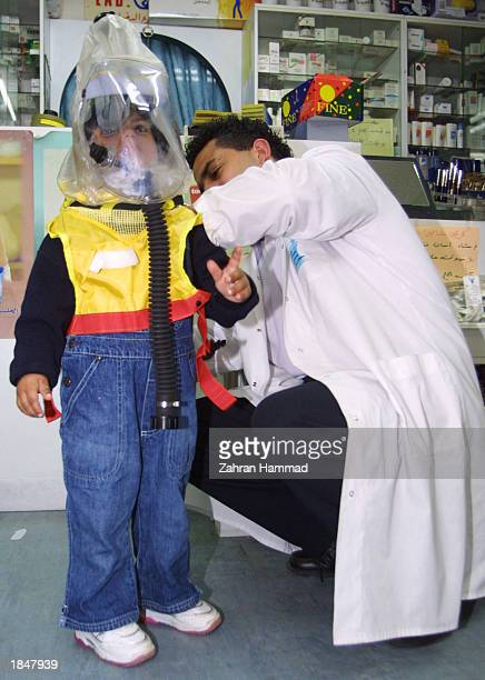 Palestinian doctor Yousef AlMemi teaches a child how use a gasmask to prepare for a possible USled war with Iraq