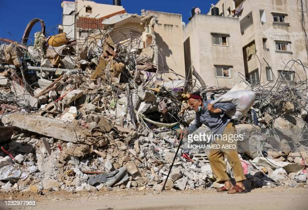 Palestinian elderly man walks past a building destroyed by Israeli bombardment in Gaza City, on May 19, 2021 - Deafening air strikes and rocket fire...