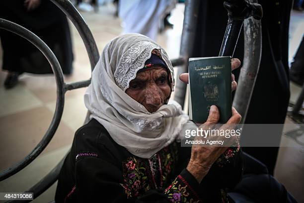 Palestinian elderly woman shows her passport as dozens of Palestinians wait for the passport check at the Palestinian side of Rafah border crossing...