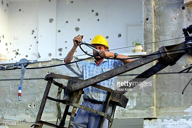 Palestinian electric worker fixes electric cable lines damaged by Israeli tank bullets during recent clashes between Palestinians and Israeli troops...