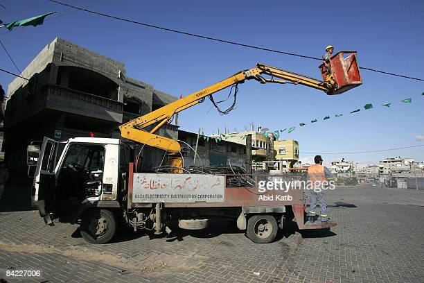 Palestinian electricians make repairs to the electricity network after it was damaged during an Israeli airstrike on January 9 2009 in the Jabalia...