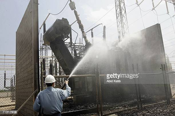 A Palestinian electricity worker extinguishes a fire inside the headquarters of the main electricity company destroyed by Israeli airstrikes June 28...