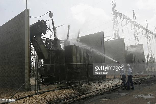 Palestinian electricity workers extinguishes a fire inside the headquarters of the main electricity company destroyed by Israeli airstrikes June 28...
