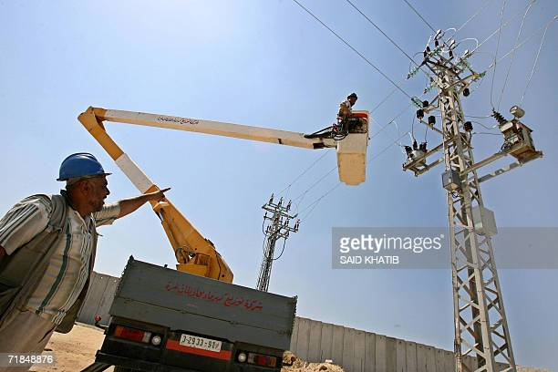 Palestinian electricity workers lay the lines close to Rafah town near the border which links the Gaza Strip and Egypt months after the main...