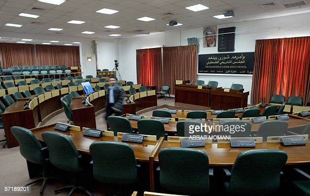Palestinian employee walks past empty seats in the Palestinian parliament in the West Bank city of Ramallah the day before the first session of the...
