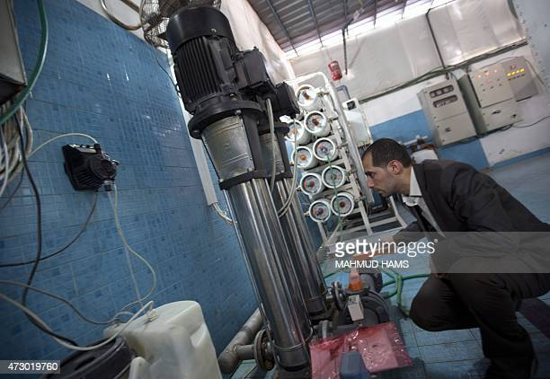 Palestinian engineer Diaa Abu Assi operates a machine that makes seawater potable on February 28 2015 in Gaza city The project uses nanotechnology to...