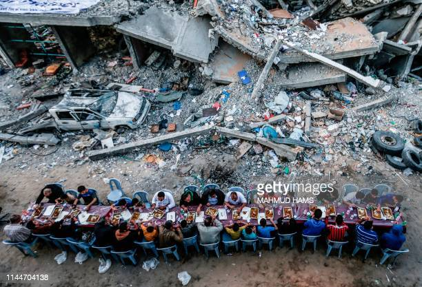TOPSHOT Palestinian families break their fast next to a building destroyed in recent confrontations between Hamas and Israel in the Gaza Strip on May...