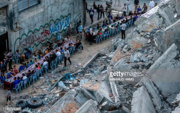 Palestinian families break their fast next to a building destroyed in recent confrontations between Hamas and Israel, in the Gaza Strip on May 18...