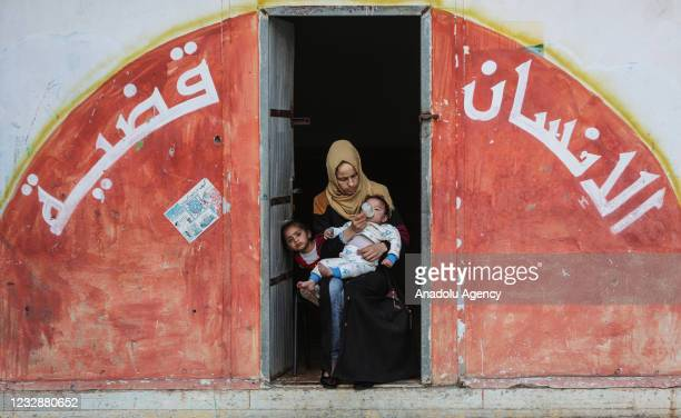 Palestinian families, fleeing from their homes with their belongings, take shelter in a school owned by the United Nations Relief and Works Agency...