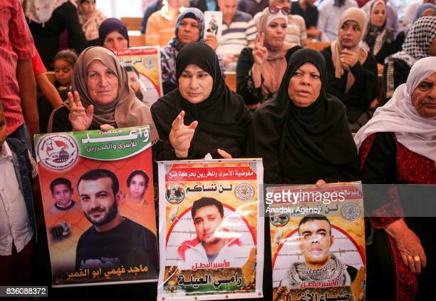 Palestinian families hold posters of their relatives as they gather for a demonstration to show their support for the Palestinian prisoners in...