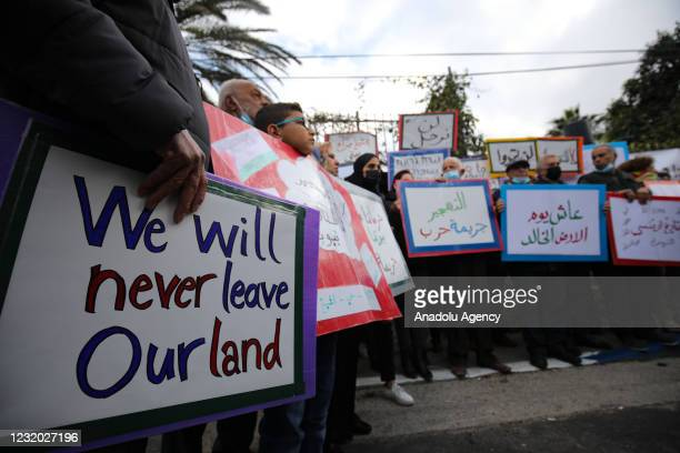Palestinian families living in Sheikh Jarrah, a predominantly Palestinian neighborhood in East Jerusalem, hold banners as they stage a demonstration...