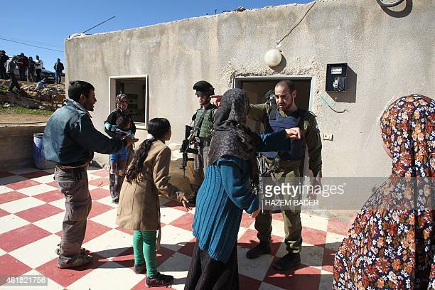 A Palestinian family argues with members of the Israeli security forces as an Israeli army bulldozer with a demolition permit prepares to pull down...