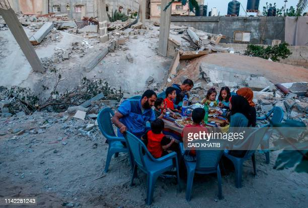 Palestinian family break their fast next to their house that was destroyed in recent confrontation between Hamas and Israel in Rafah the southern...