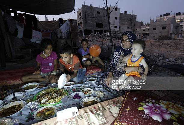 A Palestinian family gathers for iftar an elaborate meal to break Ramadan fast at the rubble of buildings a year after the 50day war between Israel...
