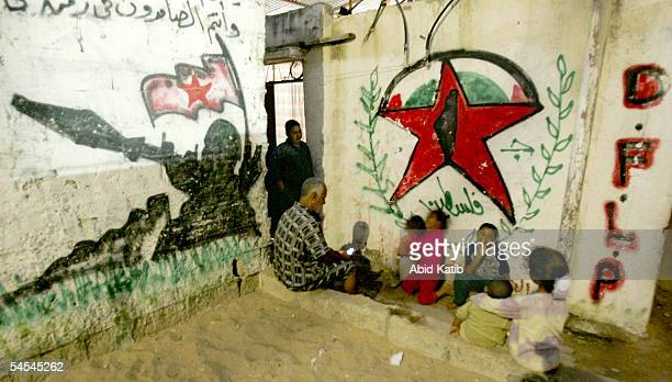 Palestinian family is seen as they sit next to the intifada graffiti in front their family home near the Jewish settlement of Neve Dekalim, September...