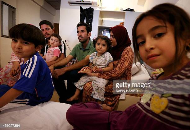 A Palestinian family living in Mosul and now fleeing violence that recently engulfed the Iraqi city gather in the room of their hotel on June 21 2014...