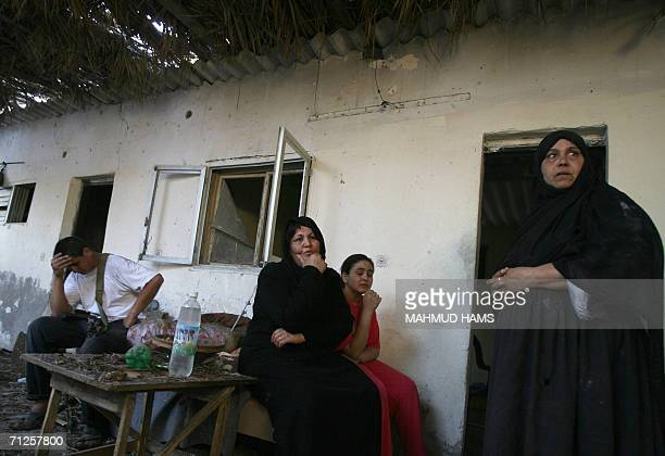 Palestinian family members sit close to where a woman was killed in her home hit during an Israeli missile strike in Khan Yunis in the southern Gaza...