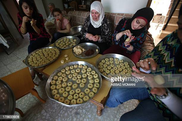 A Palestinian family prepare traditional biscuits popular on the occasion of Eid alFitr at their house in the West Bank city of Ramallah on August 5...