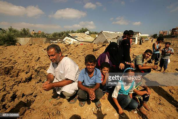 Palestinian family sit around their destructed house and nearby chicken farm after an Israeli air strike hit Rafah in the Southern of Gaza strip...