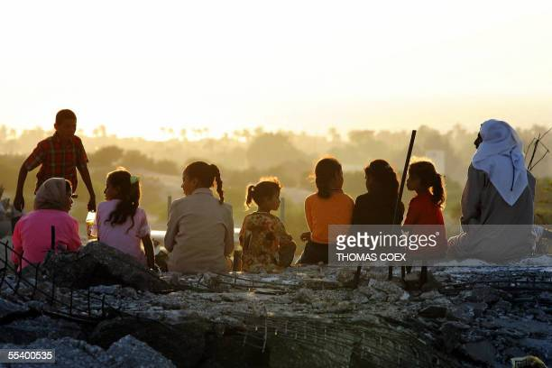Palestinian family sits on the rubble of destroyed houses in the exsettlement of Neve Dekalim in the Gaza Strip 14 September 2005 Palestinians staged...