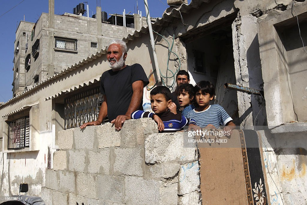 A Palestinian family stand in front of their home watching the funeral procession of killed members of the Hejazi family, including two young children, in Beit Lahia, in the northern Gaza Strip on November 20, 2012, following an Israeli air strike the Hamas Health Ministry said.