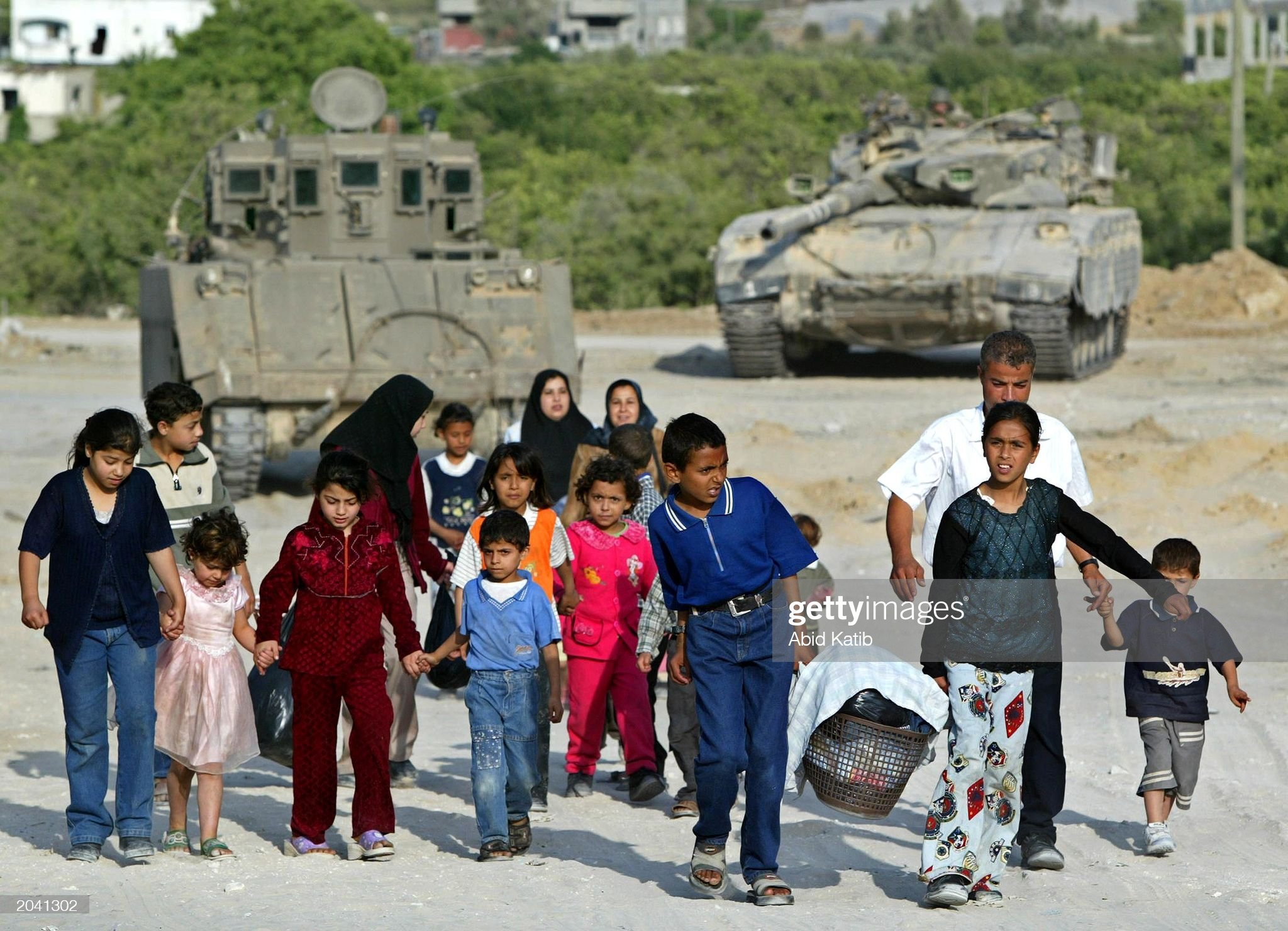 https://media.gettyimages.com/photos/palestinian-family-walks-in-front-of-israeli-tanks-may-30-2003-in-picture-id2041302?s=2048x2048