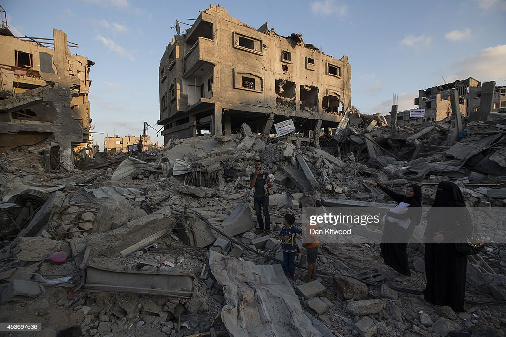 A Palestinian family walks through the rubble of a destroyed area of housing on August 16, 2014 in Gaza City, Gaza. A five-day ceasefire between Palestinian factions and Israel continues as part of efforts aimed at reaching a permanent truce deal. The Palestinian death toll from Israel's weeks-long military opparation on the Gaza Strip has risen to 1959, according to a Palestinian Health Ministry spokesman.