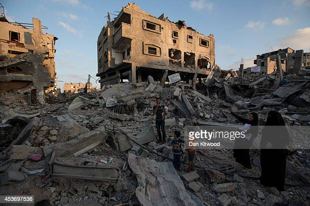 Palestinian family walks through the rubble of a destroyed area of housing on August 16 2014 in Gaza City Gaza A fiveday ceasefire between...