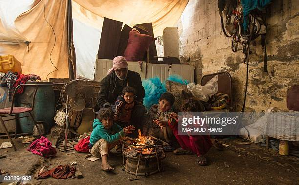 A Palestinian family warms up in front of a fire in a hovel during the cold and rainy weather in the Jabalia refugee camp in the northern Gaza Strip...