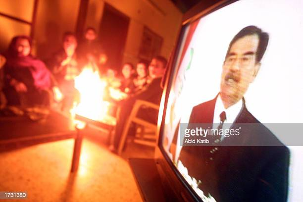 Palestinian family watch a television broadcast of Iraqi President Saddam Hussein as he speaks on the 12th anniversary of the Gulf War January 17...