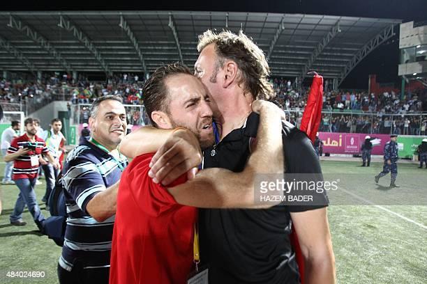 A Palestinian fan hugs Hebron's AlAhli Italian coach Stefano Cusin after their return leg football match for the Palestine Cup final on August 14...
