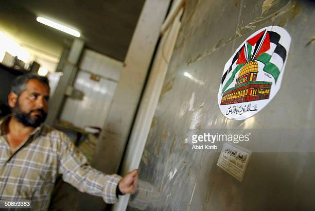Palestinian farmer closes his vegetables and flowers freezer used as a makeshift morgue marked with a sticker showing the Palestinian flag and a...