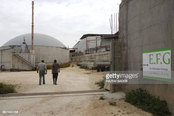 Palestinian farmer Kamal alJebrini walks by silos at the Jebrini dairy farm in the West Bank town of Hebron where cow dung is used to produce...