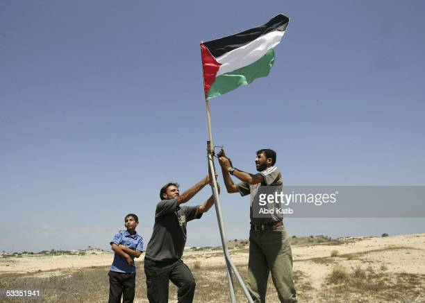 Palestinian Fatah activists place a Palestinian flag in front the Jewish settlement of Rafiah Yam during early celebrations of Israel's imminent pull...