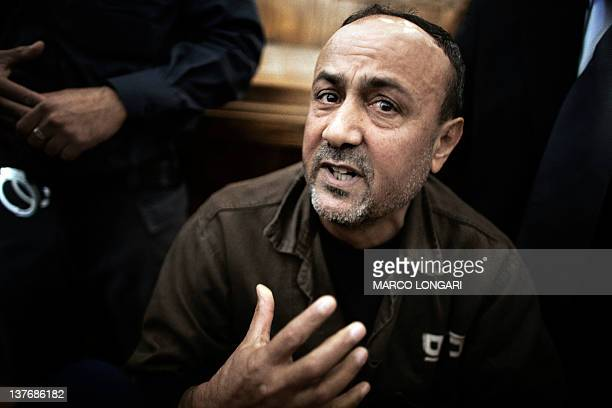 Palestinian Fatah leader Marwan Barghuti gestures inside Jerusalem's Magistrate Court where he was brought to testify as part of a US civil lawsuit...