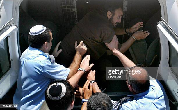 Palestinian Fatah leader Marwan Barghuti is put into a van outside Tel Aviv District Court after being sentenced June 6 2004 in Tel Aviv Israel...