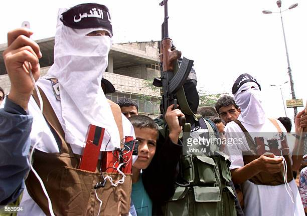 Palestinian Fateh Hamas and Islamic Jihad activists dressed as suicide bombers with fake dynamite wrapped around their bodies march April 30 2001...