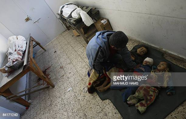 Palestinian father Hilmi alSamuli mourns over the bodies of his two sons and nephew killed by an Israeli tank shell early on January 5 upon their...