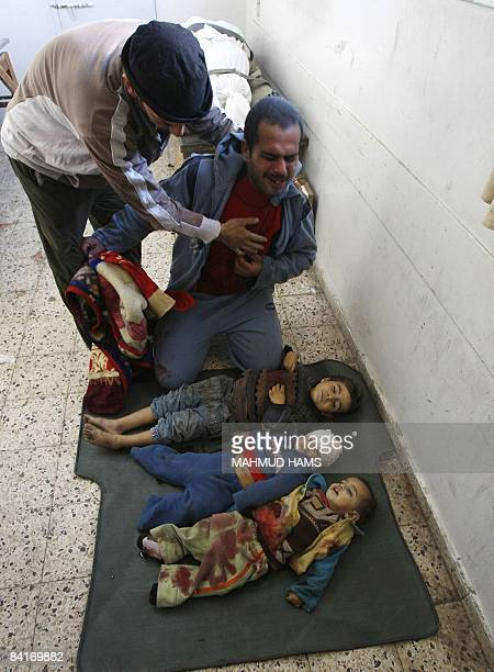 Palestinian father Magdi alSamuli mourns over the bodies of his three children killed by an Israeli tank shell early on January 5 upon their arrival...