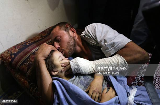 Palestinian father Yehya Hasan mourns while holding the body of his daughter Rahaf during a funeral for the toddler and her pregnant mother on...