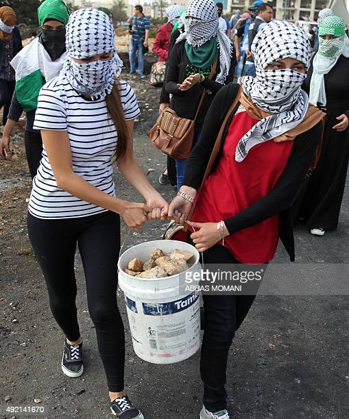Palestinian female protesters wearing Keffiehs carry a bucket of stones during clashes with Israeli security forces in Beit El Jewish settlement...