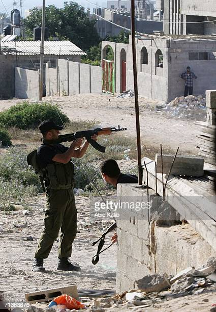 Palestinian fighter fires a gun during clashes with an Israli tank on July 6 2006 in Beit Lahia northern Gaza Strip Israeli infantry and armor...