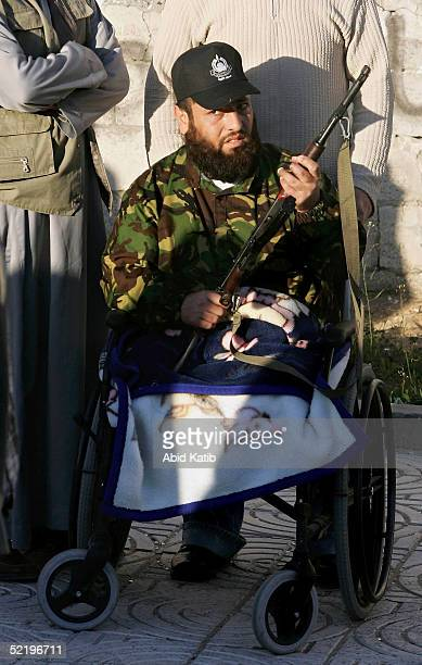 Palestinian fighter who was lost his legs during the Intifada holds a gun as he celebrates as 15 palestinian bodies arrive at the Palestinian...