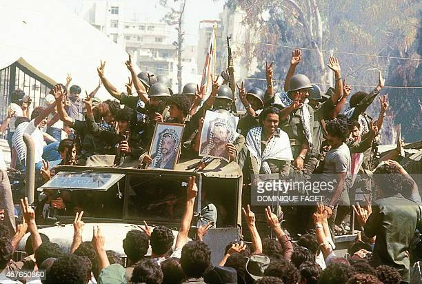 Palestinian fighters shown in a photo dated 22 August 1982 flashing Vsigns and holding portrait of their leader Yasser Arafat chairman of Palestine...