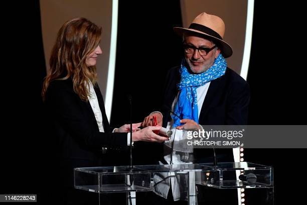 Palestinian film director and actor Elia Suleiman stands on stage next to FrenchItalian actress Chiara Mastroianni after he was awarded on May 25...