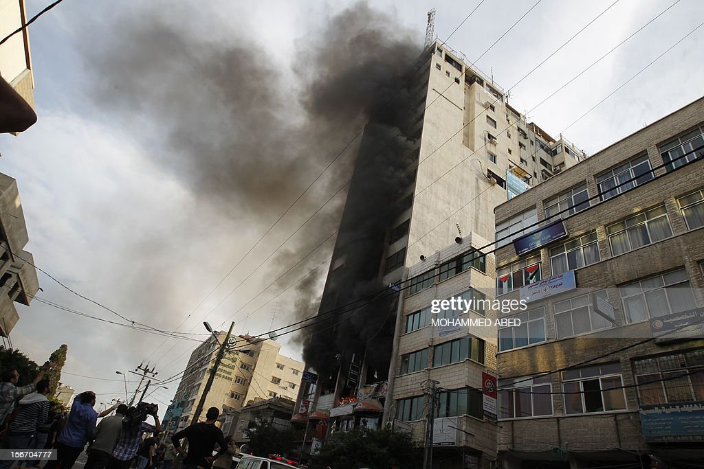 Palestinian firefighters extinguish a blaze following an Israeli air strike on the Gaza City tower housing Palestinian and international media, on November 19, 2012. Israeli air strikes killed 21 Palestinians hiking the Gaza death toll to 98 as global efforts to broker a truce to end the worst violence in four years gathered pace.