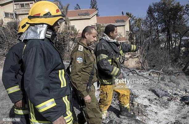 Palestinian firefighters from the West Bank city of Jenin and an Israeli security forces member arrive to help extinguish a fire in the northern...