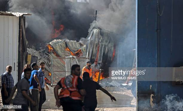 Palestinian firefighters rush to extinguish a huge fire at the Foamco mattress factory east of Jabalia in the northern Gaza Strip, on May 17, 2021.
